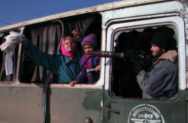 Заложники из Кизляра, удерживаемые чеченскими боевиками, машут из автобуса русским солдатам, чтобы те не стреляли. Первомайская, 10 января 1996 / AP