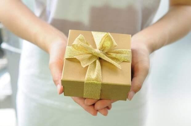 девушка держит в руках коробку с бантиком