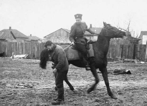 На потеху публике.  Казак-полицай на потеху оккупантам рубит шашкой пленных советских партизан. Осень 1941 года (фото)