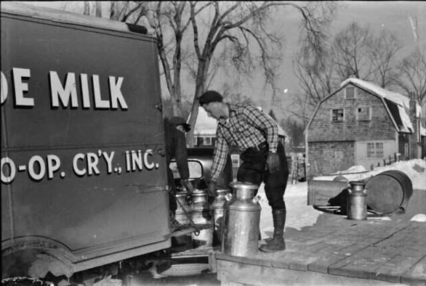 Фермеры из пригорода каждое утро рано утром привозят бидоны с молоком на перекресток, откуда его забирает грузовик и везет в город, март 1940 г.  Вудсток, штат Вермонт