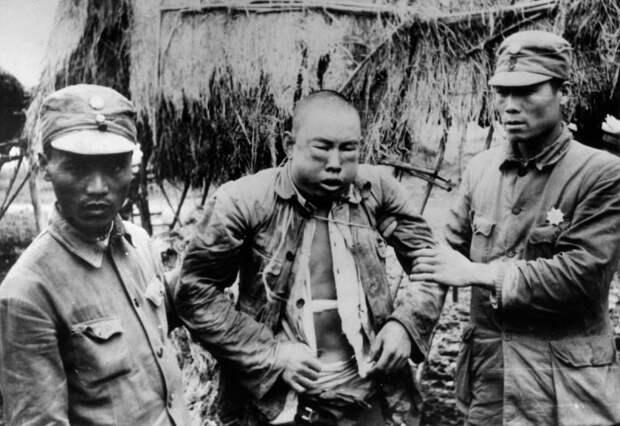 Пленный Китаец и японские солдаты на территории концлагеря в Южной Корее