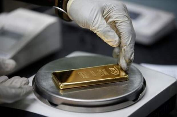 An employee weighs a 1kg gold bar at AGR (African Gold Refinery) in Entebbe, Uganda, October 4, 2018. Picture taken October 4, 2018. To match Insight AFRICA-GOLD/REFINERIES REUTERS/Baz Ratner