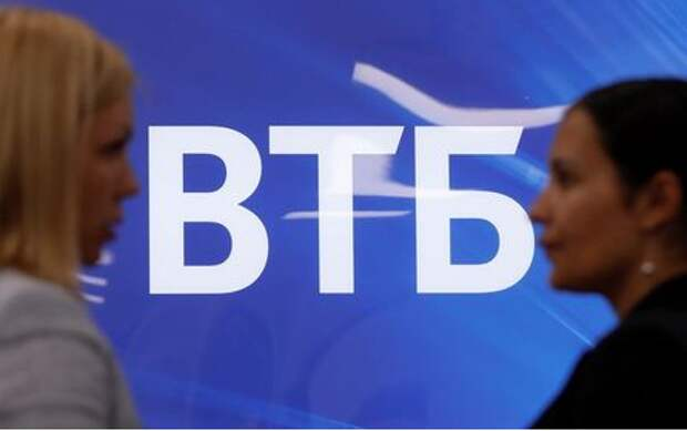Employees speak near a board with VTB logo during a tour at a branch of VTB bank in Moscow, Russia May 30, 2019. REUTERS/Evgenia Novozhenina