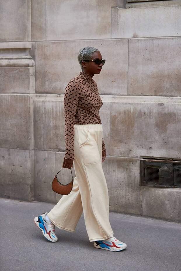 Девушка в коричневой водолазке с принтом, просторные бежевые брюки и кроссовки