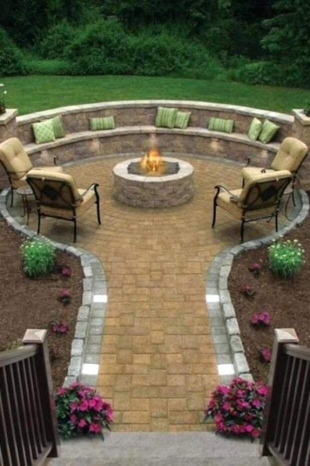 Площадка, вымощенная тротуарной плиткой с небольшим каменным очагом и элегантной мебелью из тёмной породы древесины.