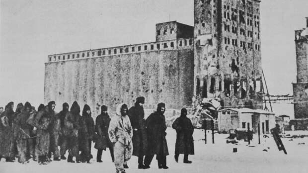 Красноармеец конвоирует колонну немецких военнопленных у здания элеватора в Сталинграде. Фото: © Военный альбом