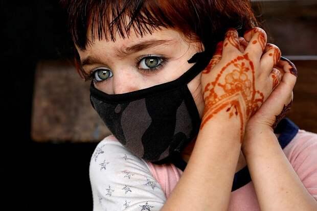 Четырехлетняя жительница Карачи, Пакистан, надевает маску перед выходом на улицу. Фото: REUTERS