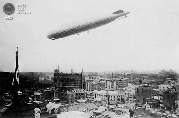 Япония. Токио. 19 августа 1929 года. «Граф Цеппелин» снижается для посадки в аэропорту Касумигаура во время первого кругосветного путешествия. (AP Photo)