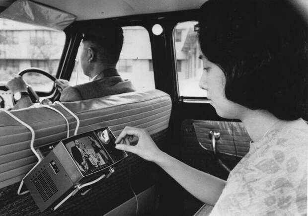 Япония, Токио, 1963 год Женщина смотрит портативный телевизор SONY (модель TV5-303) в автомобиле.