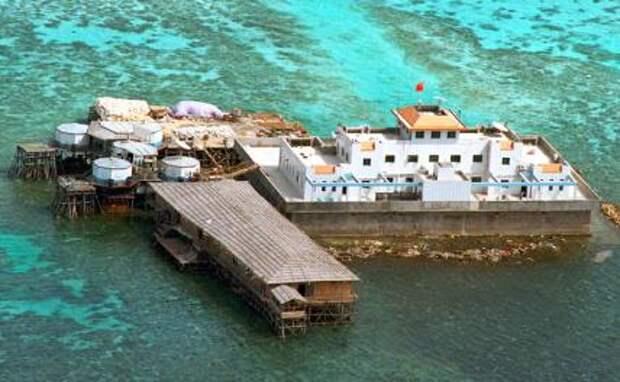 На фото: китайский флаг развевается над одной бетонных конструкций на рифе Мисчиф среди спорной группы островов Спратли в Южно-Китайском море