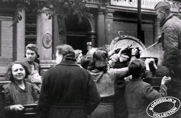 Советские солдаты кормят немцев в Берлине.