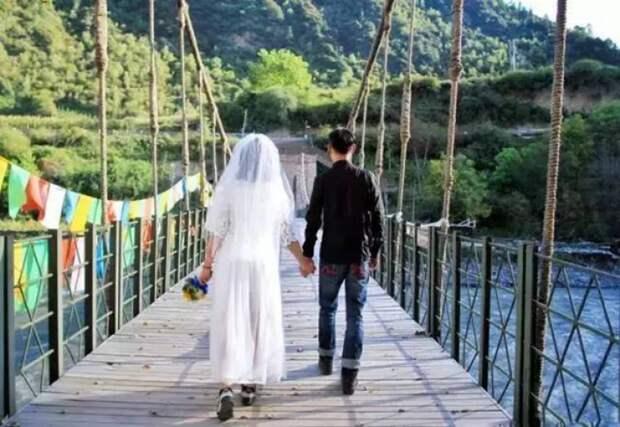 Пара фотографируется в костюмах этнических меньшинств для свадебного альбома