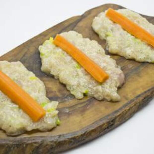 На лепешки из фарша выкладываем отваренную морковь