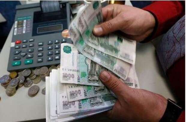 An employee counts Russian Rouble banknotes at a private company's office in Krasnoyarsk, Siberia, November 6, 2014. The rouble opened sharply weaker against both the dollar and the euro on Friday, falling over 2 percent below the previous close against both currencies. Picture taken November 6, 2014. REUTERS/Ilya Naymushin (RUSSIA - Tags: BUSINESS)