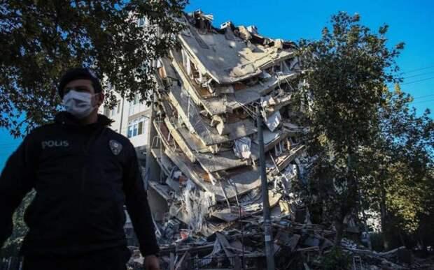 полицейский на фоне обрушившегося здания
