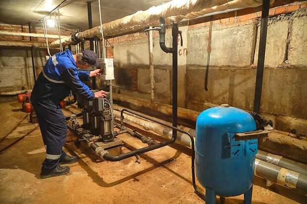 Слесарь ЖКХ во время сезонной промывкой труб горячего водоснабжения.