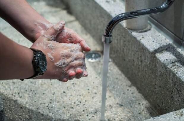 мужчина моет руки под краном