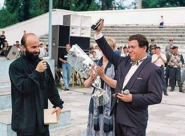 """Председатель правительства ЧРИ Шамиль Басаев вручает именной пистолет Иосифу Кобзону """"За поддержку ЧРИ""""."""