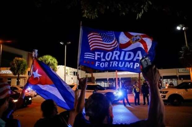 A supporter of U.S. President Donald Trump holds a Cuban flag during the 2020 U.S. presidential election, outside Versailles Restaurant at Little Havana neighborhood in Miami, Florida, U.S., November 3, 2020. REUTERS/Marco Bello