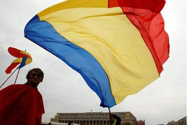 FILE PHOTO: People wave flags during a rally in front of Victoria palace, Romania's government headquarters, in Bucharest October 21, 2012.REUTERS/Bogdan Cristel/File Photo