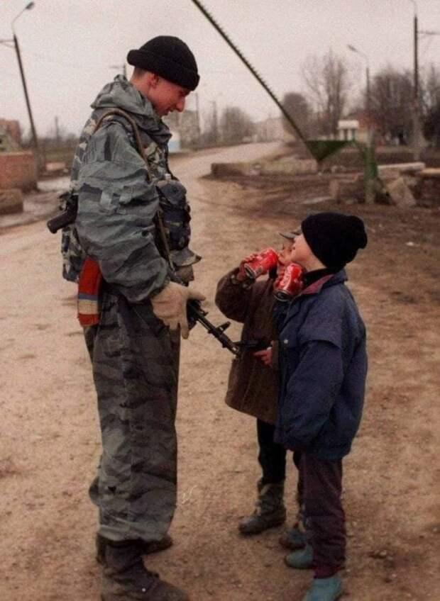 Солдат федеральных сил угощает чеченских ребят кока-колой, 1996 год