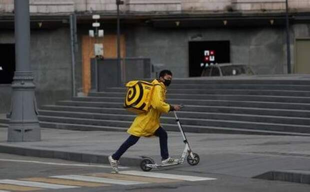 A Yandex.Eats food delivery courier wearing a protective face mask rides a scooter amid the coronavirus disease (COVID-19) outbreak in Moscow, Russia April 12, 2020. Picture taken April 12, 2020. REUTERS/Maxim Shemetov