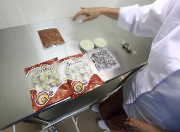 Мясо приготовленных садовых улиток (Helix Aspersa) помещают обратно в раковины и упаковывают в пакеты на ферме в Чоачи, Колумбия.